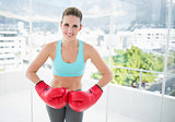 Smiling woman wearing red boxing gloves