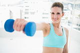 Portait of smiling woman exercising with dumbbell