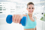 Smiling woman exercising with dumbbell