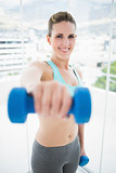Fit smiling woman exercising with dumbbell