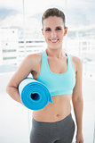 Smiling woman holding exercise mat