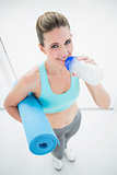 Woman in sportswear drinking and holding exercise mat