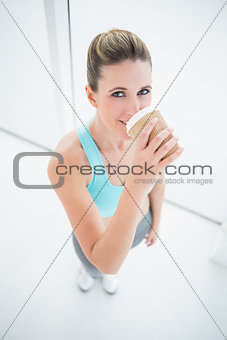 Fit woman in sportswear drinking coffee
