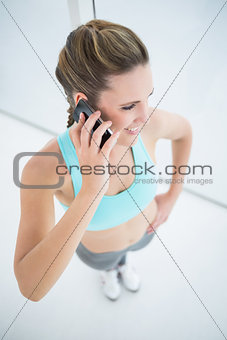 Fit woman in sportswear talking on mobile phone