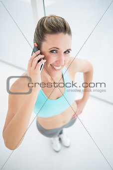 Fit smiling woman talking on mobile phone