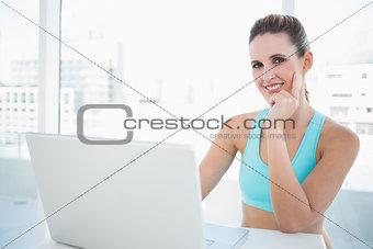 Thoughtful woman in sportswear using laptop