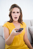 Surpised woman holding remote control