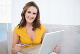 Smiling woman holding laptop and credit card