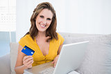 Smiling woman holding laptop showing credit card