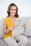 Smiling woman holding newspaper