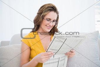 Peaceful woman wearing glasses reading newspaper
