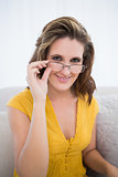 Attractive woman wearing glasses sitting in living room