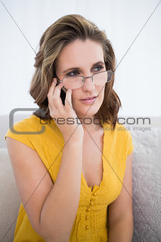 Thoughtful woman wearing glasses talking on the phone