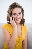 Smiling woman with glasses talking on the phone