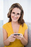 Happy woman with glasses holding phone