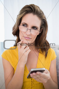 Thoughtful woman using phone