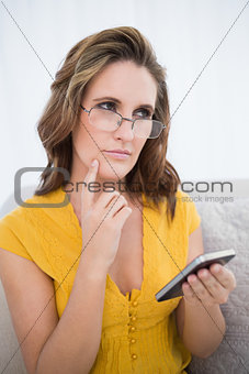 Thoughtful pretty woman with glasses holding phone