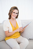 Smiling woman with glasses using tablet computer