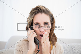 Astonished pretty woman having a phone call