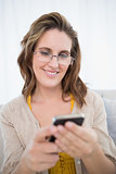 Smiling attractive woman wearing glasses using phone