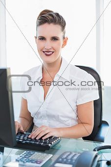 Smiling businesswoman working on computer looking at camera