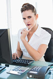 Thoughtful pretty businesswoman working on computer
