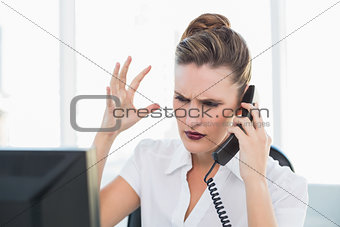 Angry stylish businesswoman on the phone