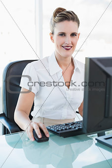 Smiling classy businesswoman working on computer