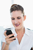 Close up view on smiling businesswoman using smartphone