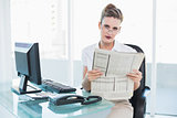 Serious businesswoman wearing glasses holding a newspaper