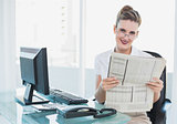 Smiling businesswoman holding newspaper