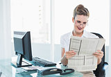 Smiling businesswoman wearing glasses reading newspaper