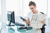 Unsmiling businesswoman holding newspaper and using calculator