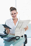 Cheerful classy businesswoman holding calculator and newspaper