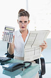 Serious businesswoman holding newspaper and showing calculator