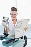 Smiling businesswoman showing calculator at camera