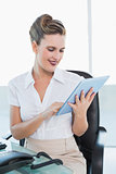 Cheerful classy businesswoman using her digital tablet