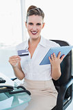 Happy stylish businesswoman holding tablet pc and credit card