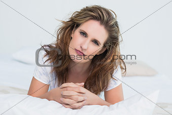 Portrait of serious woman lying on bed