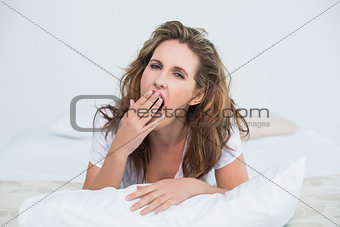 Tired woman resting in bed