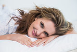 Smiling woman lying on cosy bed