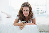 Smiling woman resting in bed text messaging