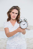 Frowning tired woman showing alarm clock
