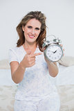 Smiling woman sitting on bed pointing at alarm clock