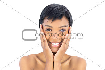 Joyful black haired woman posing holding her head