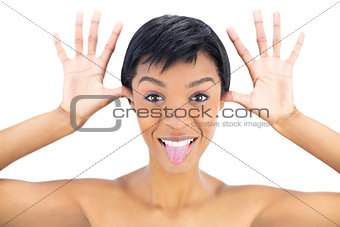 Joyful black haired woman posing with tongue out and hands around her head