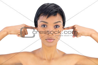 Serious black haired woman clogging her ears