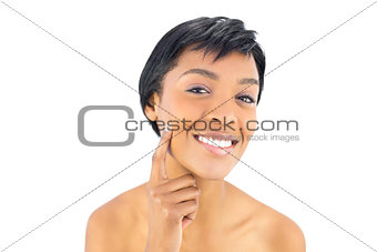 Cheerful black haired woman posing with a finger on her cheek