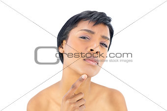Thoughtful black haired woman posing with a finger on her chin