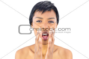 Upset black haired woman shouting with hands around the mouth